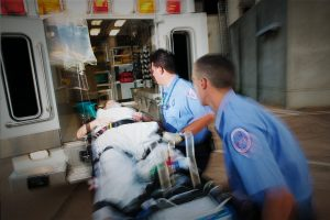 EMTs loading a patient into an ambulance