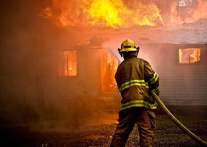 Firefighter spraying water on a blazing house