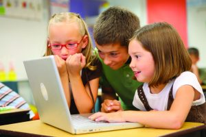Two young girls and a boy use a laptop computer