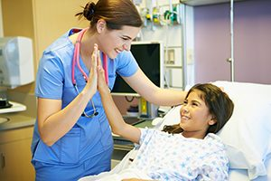 Happy Young Girl Talking To Smiling Female Nurse In Hospital Room