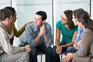 Meeting Of Support Group Looking At Each Other Talking