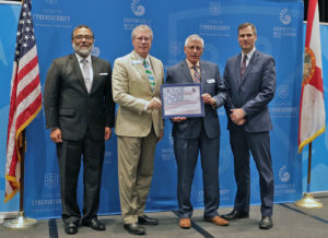 Photo of Dr. Carstens and Stephen Miller receiving Center of Excellence certificate