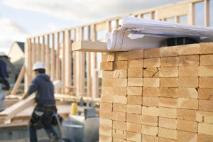 Photo of construction site, worker, stacks of lumber